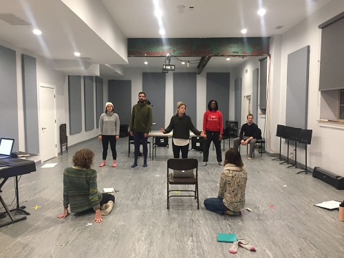 IMAGE: Two people sit with their backs to the camera in a rehearsal room. They are watching five actors rehearse a scene where they are all standing downstage looking out toward the audience.